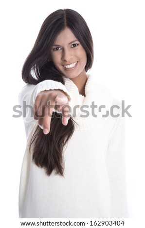 Beautiful dark hair young woman is showing something with her index finger - long black hair and smiling in a white wool pullover. - stock photo