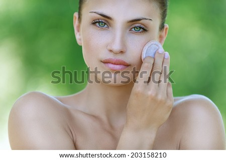 Beautiful dark-haired calm young woman handles face creams, against background of summer green park.