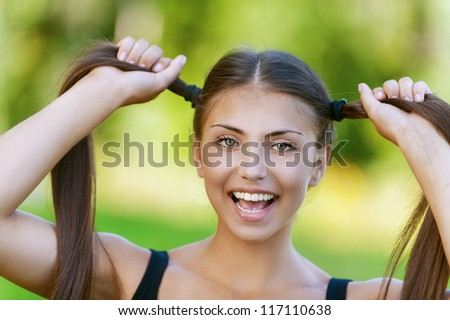 Beautiful dark-haired funny young woman holds up their tails, against background of summer green park. - stock photo