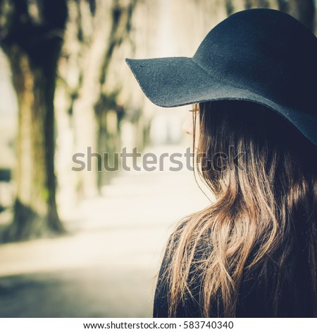 Beautiful dark-haired girl alone at cemetery, wearing black hat. Rear view.