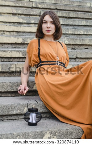 Beautiful dark-haired girl in a long dress sitting on stairs
