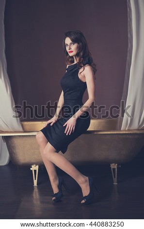 Beautiful dark-haired girl in black evening dress sitting on the edge of the bath, luxury, temptation