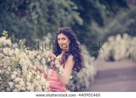 Beautiful dark-haired girl with long hair in the lush spring garden - stock photo