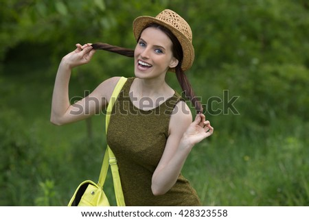 Beautiful dark-haired happy young woman with backpack , against background of summer green park.