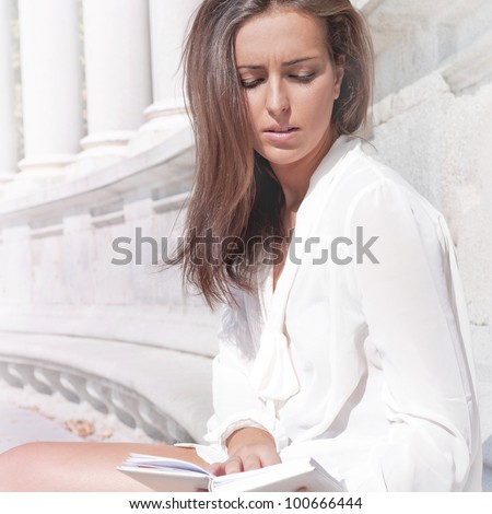 Beautiful dark-haired pretty girl in jeans and white blouse reads white book against Renaissance building of museum or gallery - stock photo