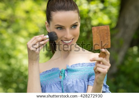 Beautiful dark-haired smiling young woman treats her face with brush and mirror, against background of summer green park. - stock photo