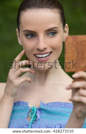 Beautiful dark-haired smiling young woman treats her face with mirror, against background of summer green park. - stock photo