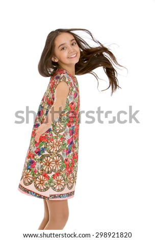 Beautiful dark haired teen girl Oriental appearance in a short colorful dress whirls around, close-up-Isolated on white background - stock photo