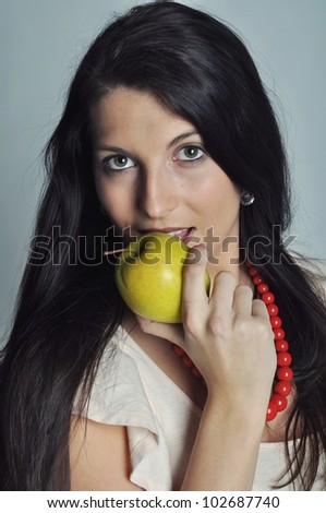 Beautiful dark-haired woman holding yellow apple