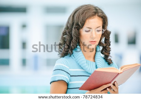 Beautiful dark-haired woman in blue sweater and glasses reads interesting red book against spacious hall.