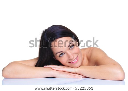 Beautiful dark haired woman resting her head on her hands against a white background - stock photo