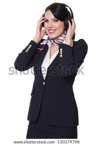 Beautiful dark haired young business woman dressed in a dark blue suit with a purple scarf and white shirt standing smiling and holding her earphones with both her hands, isolated on white background - stock photo