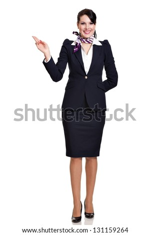 Beautiful dark haired young business woman dressed in a dark blue suit with a purple scarf standing and showing to her upper right side with two fingers, isolated on white background - stock photo