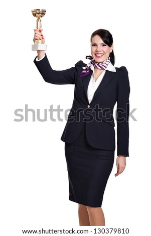 Beautiful dark haired young business woman dressed in a navy suit with a purple scarf and white shirt standing smiling and lifting a sports cup in the air, isolated on white background - stock photo