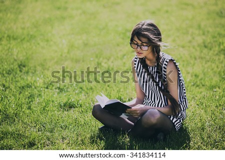 Beautiful Dark-haired Young Woman Sits On Grass And Reading Book, Against Summer Green Park.