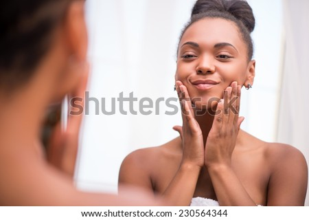 Beautiful dark skinned girl in white towel bringing face cream looking at mirror admiring  herself  touching cheeks smiling  isolated on white background - stock photo