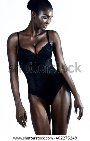 Beautiful dark-skinned young woman sensualy posing in black lingerie. Fashion Photoshoot
