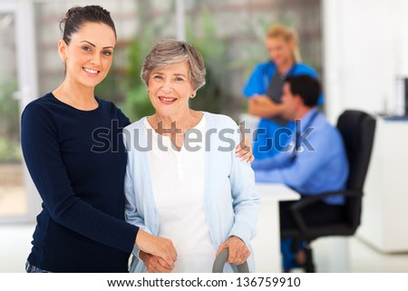 beautiful daughter and her senior mother in doctors office - stock photo