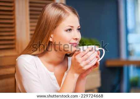 Beautiful day dreamer. Side view of thoughtful young woman enjoying coffee in cafe  - stock photo