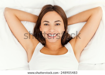 Beautiful day dreamer. Top view of beautiful young woman holding hands behind head while lying in bed and smiling