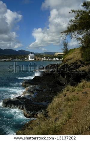 Beautiful day on Kauai, Hawaii.  In distance cruise ship is docked.  Rocky shoreline with splashing waves.  Vivid blue skies. - stock photo