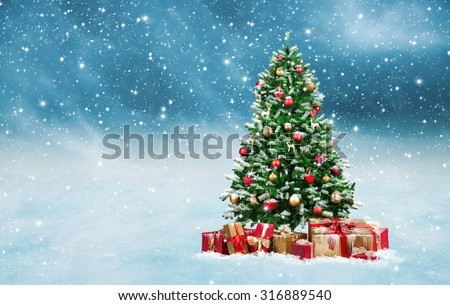 Beautiful decorated christmas tree with present boxes in a winter landscape with snow