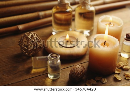 Beautiful decorated composition with candles, pebbles and bamboo on wooden background, close up