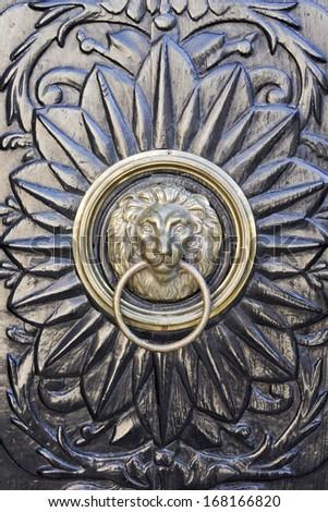 Beautiful decorated door knocker with lion's head - stock photo
