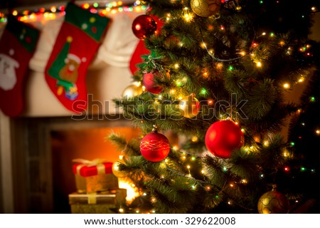 Beautiful decorated fireplace and Christmas tree at cottage - stock photo
