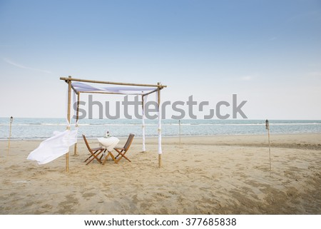 Beautiful Decorated Romantic Table on Sandy Beach at Sunset. - stock photo