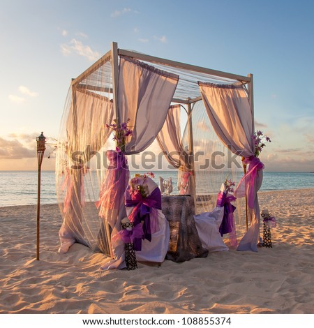 Beautiful Decorated Romantic Wedding Table on Sandy Tropical Caribbean Beach at Sunset