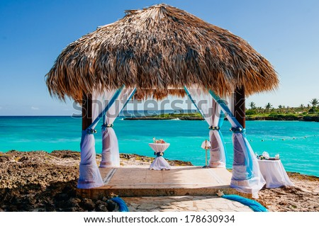 Beautiful Decorated Romantic Wedding Table on Sandy Tropical Caribbean Dominican Beach at Sunset. Wedding arch decorated on caribbean beach. gazebo for wedding ceremony on the coast - stock photo