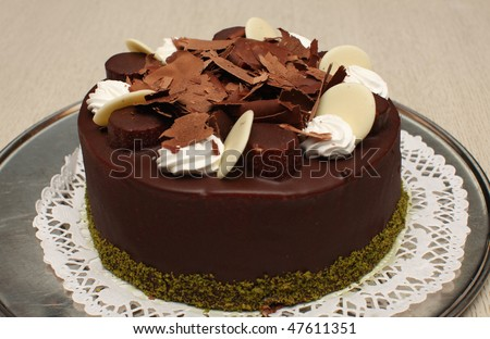 Beautiful decorated round chocolate cake with bananas and pieces of white and brown chocolate - stock photo