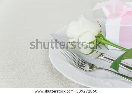 Beautiful decorated table with white plates, gift box with a pink ribbon, cutlery and white rose flower on tablecloths, with space for text