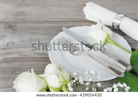 Beautiful decorated table with white plates, linen napkin, cutlery and white rose flowers on an old wooden table - stock photo