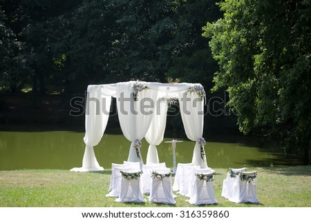 Beautiful decorated with light white chiffon chandelier and bouquets of roses pastel colors wedding pavilion chairs and table standing on green grass near lake and trees sunny day, horizontal picture - stock photo