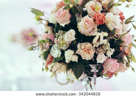 Beautiful decoration on wedding table with roses in bouquet - stock photo