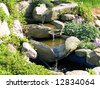 Beautiful decorative home garden stone waterfall pond - stock photo