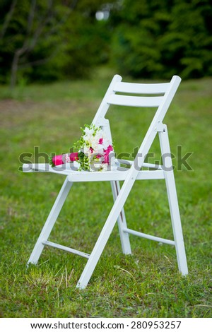 Beautiful delicate bridal bouquet lying on the white summer chair.