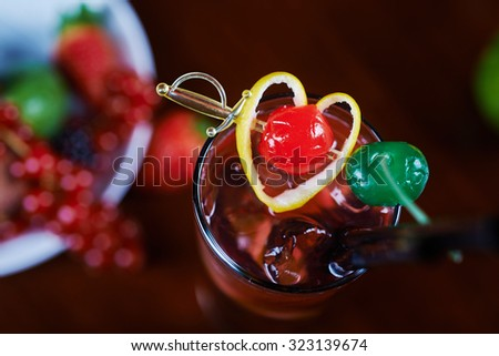 beautiful delicious alcoholic cocktail or lemonade in a glass with a backdrop of the heart with berries and Fruit on a table in a restaurant with backgrounds of bright colorful lights. soft focus. - stock photo