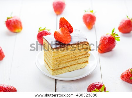 Beautiful delicious homemade cake with strawberries on white wooden table. - stock photo