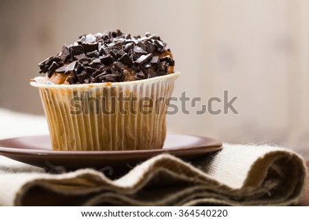 Beautiful delicious tasty fattening bakery cupcake in muffin paper with chocolate chips on top standing on sackcloth textile indoor closeup copyspace on blur background, horizontal picture - stock photo