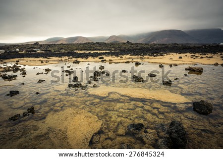 beautiful desert mountain landscape with water on the island of Lanzarote, Canary Islands - stock photo