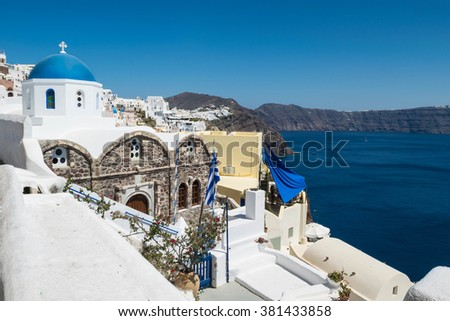 Beautiful details of Santorini island - typical houses and church with white walls, white stones and blue sea Greece - stock photo