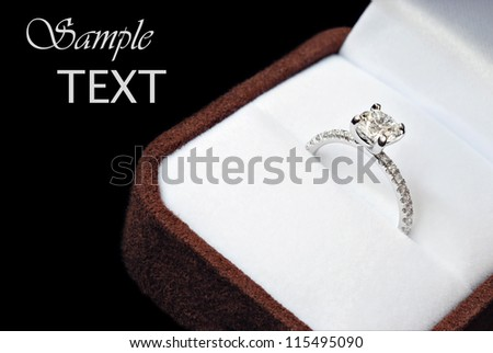 Beautiful diamond engagement ring in suede jeweler's box on black background with copy space.  Macro with shallow dof. - stock photo