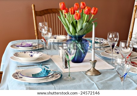 Beautiful dinner table with china and tulips