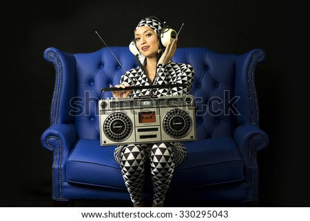 beautiful disco woman in black and white suit posing with vintage ghettoblaster