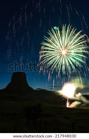 beautiful display of fireworks with Devils Tower national monument silhouetted in the background - stock photo