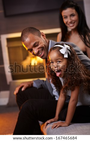 Beautiful diverse family having fun at home, little daughter sticking tongue, smiling. - stock photo