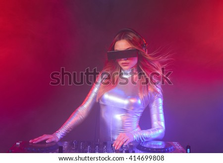 Beautiful DJ girl on decks at the party